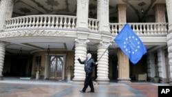 Một người biểu tình cầm cờ Liên hiệp châu Âu trước nhà của Tổng thống bị lật đổ Viktor Yanukovych ở Mazhyhirya cách thủ đô Kyiv khoảng 20 kilomet về hướng bắc
