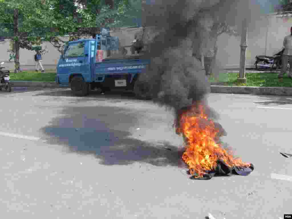 Angry protesters set fire to clothes belonging to security guards after the guards left them and fled the scene, Phnom Penh, Cambodia, July 15, 2014. (Khoun Theara/VOA)