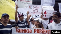 Protesters in front of a social security office hold placards demanding medicine in Caracas, Venezuela, Aug. 27, 2015.