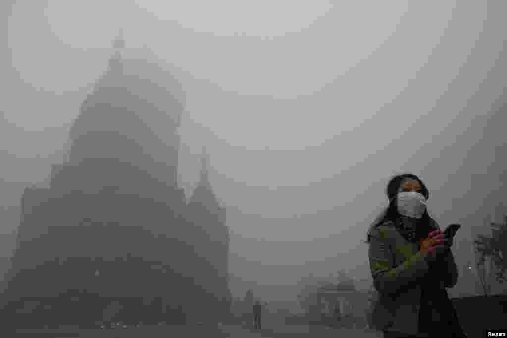 A woman wearing a mask checks her mobile phone during a smoggy day on the square in front of Harbin's landmark San Sophia church, China, Oct. 21, 2013.