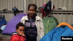 Tsega, 38 ans, qui a fui l'Érythrée il y a six ans, pose avec son fils Naher, 5, devant leur tente dans un refuge pour migrants à Calais, dans le nord de la France, le 28 octobre 2014.