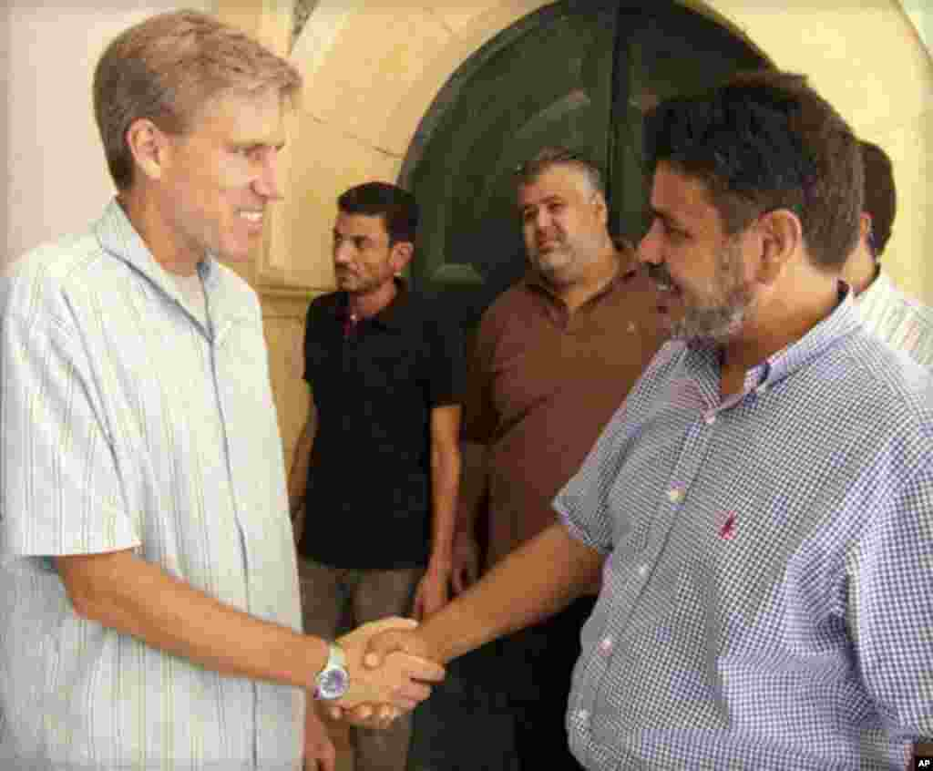 Elchi Kris Stivens liviyaliklar bilan qo'l berib ko'rishmoqda. Tripoli, 27-avgust, 2012-yil.