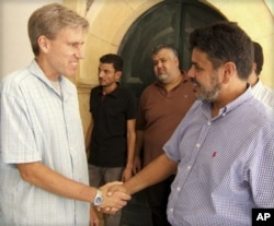 FILE – The late U.S. Ambassador to Libya Chris Stevens, left, greets a Libyan man in this photo posted on the U.S. Embassy Tripoli Facebook page on Aug. 27, 2012.