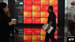 Para pengunjung melintas di depan layar yang menunjukkan data perdagangan Bursa Efek Indonesia (IDX), di Jakarta, 9 Maret 2020. (Foto: AFP)