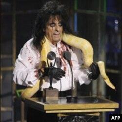 Alice Cooper, với con rắn đeo trên cổ, lên sân khấu phát biểu tại buổi lễ gia nhập câu lạc bộ