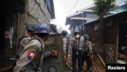防暴警察在緬甸西部佛教徒與基督徒之間衝突的現場
