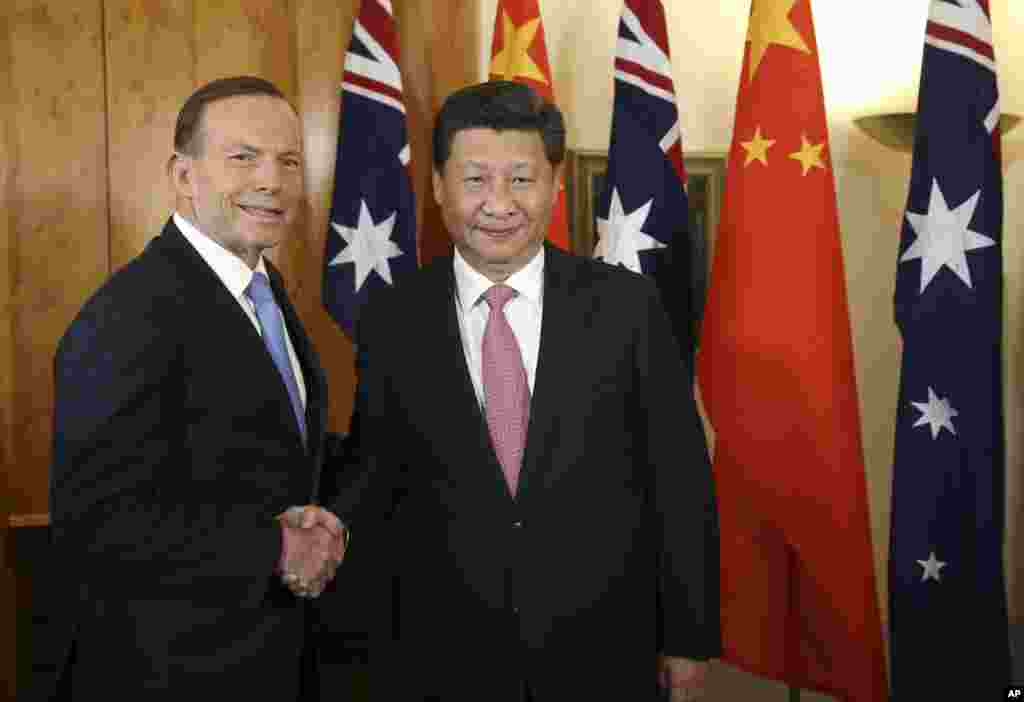 Chinese President Xi Jinping and Australian Prime Minister Tony Abbott shake hands at the start of their bilateral meeting at Parliament House in Canberra, Australia, Nov. 17, 2014.