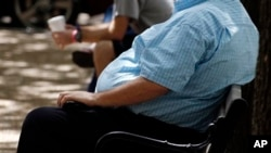 FILE - An overweight man rests on a bench in Jackson, Missouri.