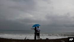 FILE - A couple watches the sea under rain in Kingston, Jamaica, Oct. 2, 2016. A depression in the southwestern Caribbean region is expected to become a tropical storm later in the day or overnight, the U.S. National Hurricane Center says.