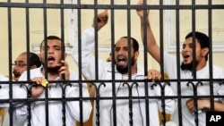 Supporters of the Muslim Brotherhood and other Islamists call out from the defendants cage as they receive sentences ranging from death by hanging for one, life in prison for 13 and 8-15 years for the others after they were convicted of murder, rioting, and violence in a mass trial in Alexandria, Egypt, May 19, 2014.
