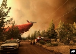 This photo provided by the Oregon Department of Forestry shows a firefighting tanker dropping fire-fighting materials over the Grandview Fire near Sisters, Oregon, July 11, 2021. (AP Photo)