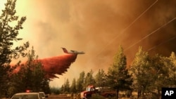 This photo provided by the Oregon Department of Forestry shows a firefighting tanker making a retardant drop over the Grandview Fire near Sisters, Ore., July 11, 2021.