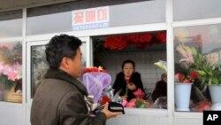 Seorang pria membeli bunga untuk merayakan Hari Ibu di distrik Mansudae, Pyongyang. (Foto: Dok)