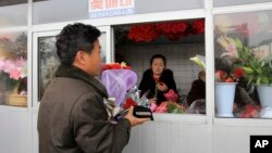 FILE - A North Korean man purchases a bouquet of carnations at a flower stand in the Mansudae District of downtown Pyongyang, North Korea.