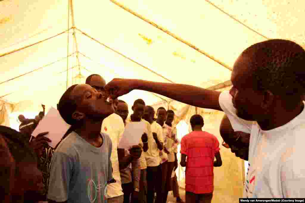 A displaced youth is given a dose of oral cholera vaccine at the Tomping UNMISS base in Juba. Faith-based humanitarian group Medair along with the South Sudan Ministry of Health, WHO, UNICEF and MSF are vaccinating IDPs pre-emptively against cholera.