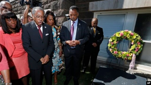 Rev. Julius Scruggs, second from left, leads people in prayer during a wreath laying ceremony at the 16th Street Baptist Church
