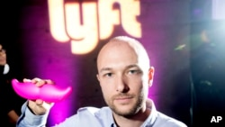 "FILE - In this Monday, Jan. 26, 2015, file photo, Logan Green, co-founder and chief executive officer of Lyft, displays his company's ""glowstache"" during a launch event in San Francisco. On Monday, Jan. 4, 2016, General Motors Co. announced it is investing $500 million in ride-sharing company Lyft Inc. GM gets a seat on Lyft's board as part of the partnership, which could speed the development of on-demand, self-driving cars."