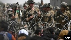 Para tentar AS berjaga di balik kawat berduri, sementara warga Afghan duduk di pinggir jalan dekat kawasan militer Bandara Internasional Kabul, 20 Agustus 2021.