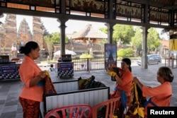 Para pedagang perempuan menyiapkan kain sarung menunggu wisatawan yang sepi di Candi Puseh, Desa Batuan, Gianyar, Bali (5/2).