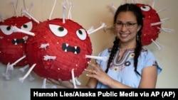 In this photo provided by Alaska Public Media, Carolina Tolladay Vidal displays custom COVID-19 piñatas in her home in Anchorage, Alaska, on April 14, 2021. (Hannah Lies/Alaska Public Media via AP)