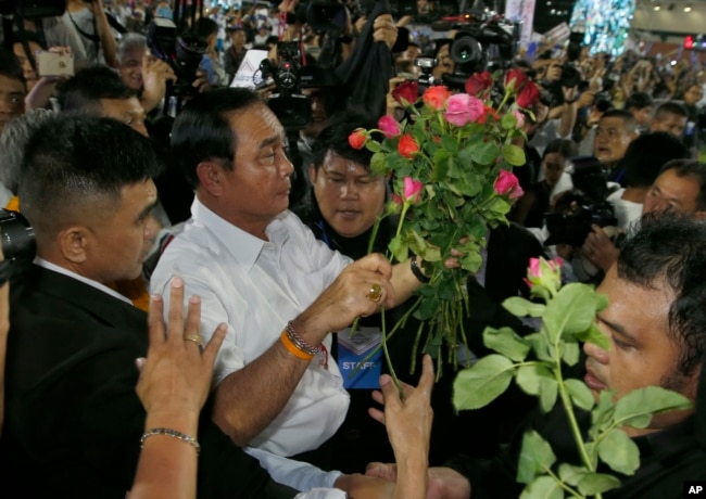 Prayut Chan-ocha of the Palang Pracharat Party receives flowers from supporters during an election campaign rally in Bangkok, Thailand, March 22, 2019.