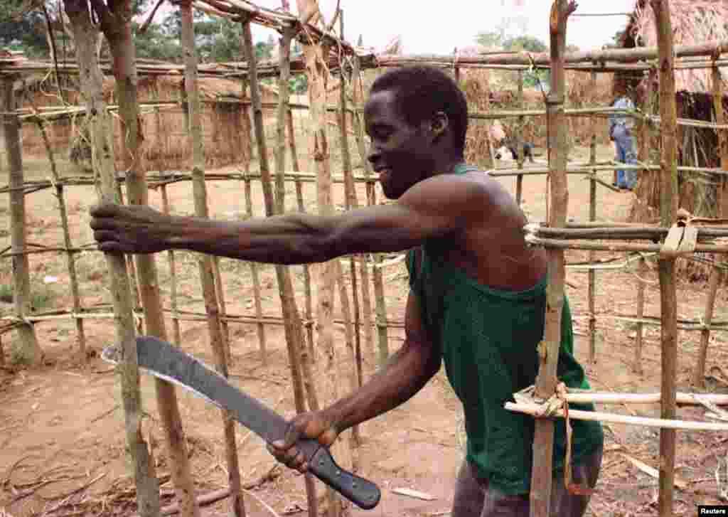 Refugiado angolano constroi um abrigo no acampamento de Caxito, onde 14 mil pessoas se refugiam da sangrenta guerra civil em Angola. Foto de 1998.