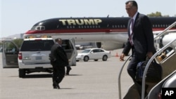 Republican presidential candidate, former Massachusetts Governor Mitt Romney walks past Donald Trump's airplane as he arrives in Las Vegas, May 29, 2012.