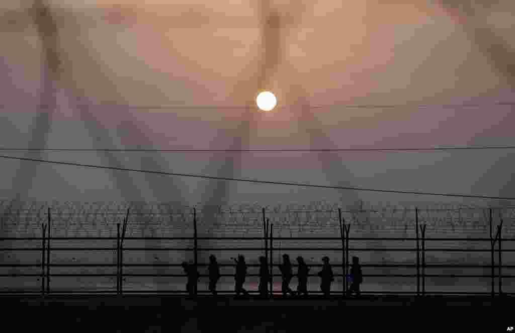 Binh sĩ Nam Triều Tiên tuần tra dọc một hàng rào dây kẻm gai vào lúc hoàng hôn tại Paju, phía bắc Seoul, gần ranh giới làng Panmunjom chia cách hai nước Triều Tiên kể từ cuộc chiến tranh Triều Tiên. Các xe buýt chở du khách vẫn đến thăm vùng biên giới được phòng thủ cẩn mật, ngay cả khi chính phủ hai bên đe dọa biến đối thủ thành đống gạch vụn.
