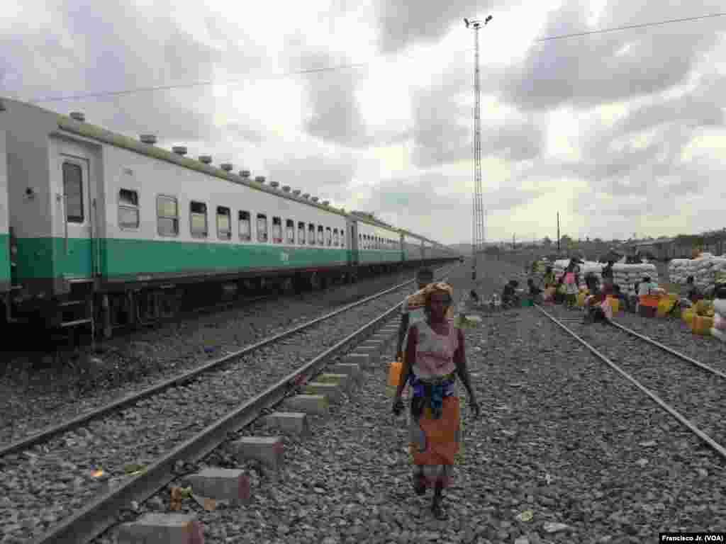 Uma mulher caminha ao lado da linha férra na estação dos Caminhos de Ferro de Moçambique em Moatize