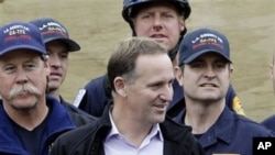 New Zealand's PM John Key, center, meets with relief workers from US during a tour of a tent city where hundreds of international and local relief workers have been housed in central Christchurch following Tuesday's earthquake in New Zealand, February 26,
