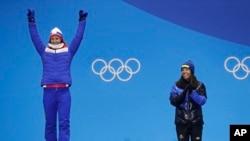 Charlotte Kalla (Swedia), tengah, peraih medali emas pertama Olimpiade Musim Dingin di PyeongChang 2018 untuk kategori Women's cross-country 7.5/7.5 kilometer skiathlon, bertepuk tangan seusai Marit Bjoergen (Norwegia) menerima medali peraknya, pada upacara penyerahan medali, 10 Februari 2018.