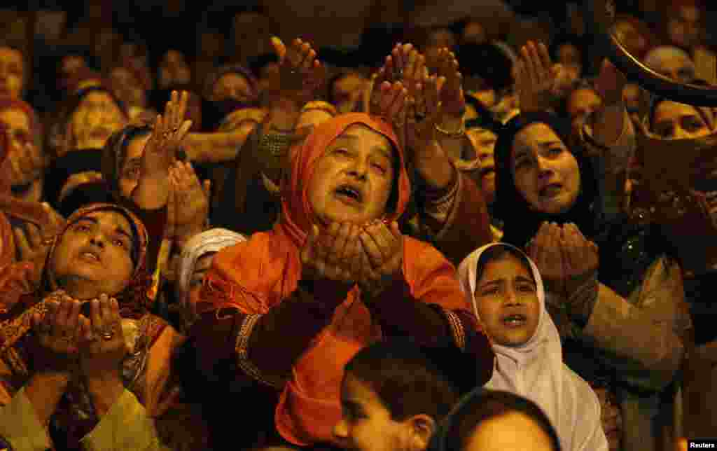 Kashmiri Muslims raise their arms upon seeing a relic of Sheikh Abdul Qadir Jeelani, a Sufi saint, being displayed to devotees at his shrine in Srinagar, India.