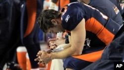 Denver Broncos quarterback Tim Tebow (15) prays while sitting on the bench late in the fourth quarter of an NFL football game against the Kansas City Chiefs, January 1, 2012, in Denver.
