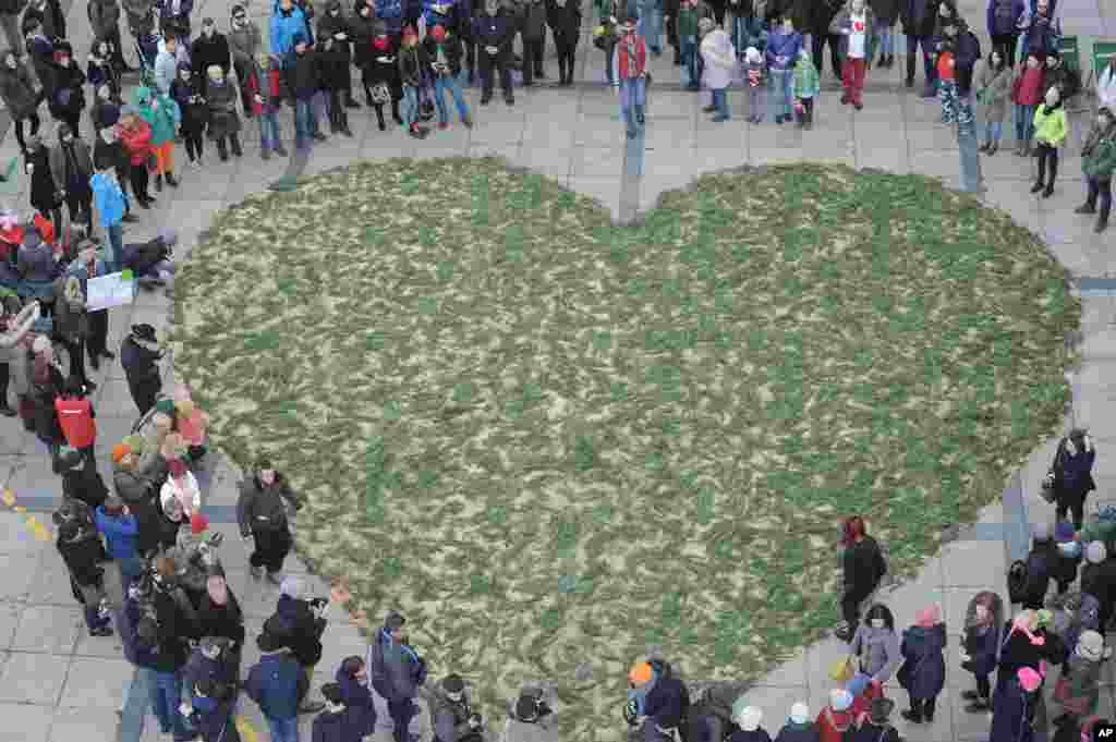 People surround a green heart made of small branches to expressing their feelings towards the Bialowieza forest, considered the last primeval forest on the European plain, during an event on Valentine's Day, in Warsaw, Poland.