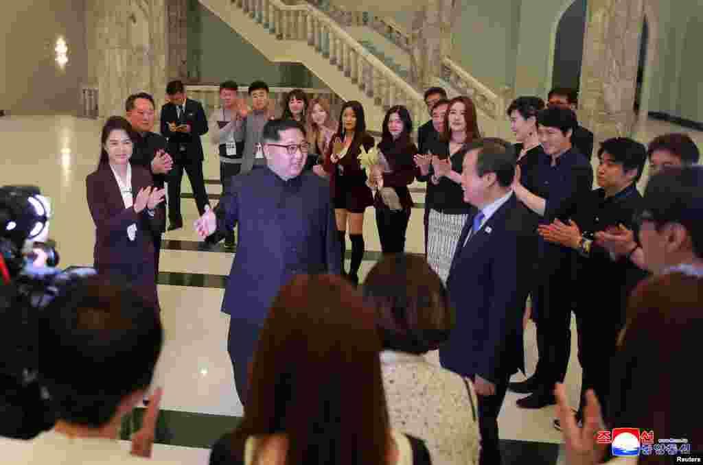 """2018年4月1日,朝鲜领导人金正恩和他的妻子在朝鲜东平壤大剧院举行的一个名为""""春天来临""""的音乐会上会见韩国K-pop歌手等人 (朝鲜中央通讯社照片)。此前,朝鲜艺术团在平昌冬奥会期间访韩演出时,韩国总统文在寅曾到场观看。韩国的韩联社报道,金正恩星期天说,文在寅总统观看了韩朝合演,他至少应看一场演出才算礼尚往来。"""