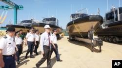 """美國駐河內大使館公佈的這張照片顯示,美國大使泰德·奧索斯(中)與越南海岸警衛隊人員在2017年5月22日在越南中部廣南舉行的轉交儀式中一道視察美國送交的""""金屬鯊魚""""巡邏艇。"""