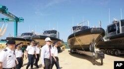 """美国驻河内大使馆公布的这张照片显示,美国大使泰德·奥索斯(中)与越南海岸警卫队人员在2017年5月22日在越南中部广南举行的转交仪式中一道视察美国送交的""""金属鲨鱼""""巡逻艇。"""