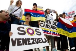 FILE - Demonstrators who oppose the Venezuelan government chant outside the Organization of American States (OAS) in Washington, during a special meeting of its permanent council.