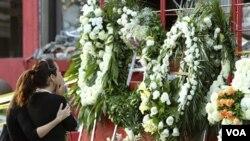Keluarga para korban tewas pembakaran sebuah kasino 'Casino Royale' berdoa di depan karangan bunga di Monterrey, Meksiko (27/8).