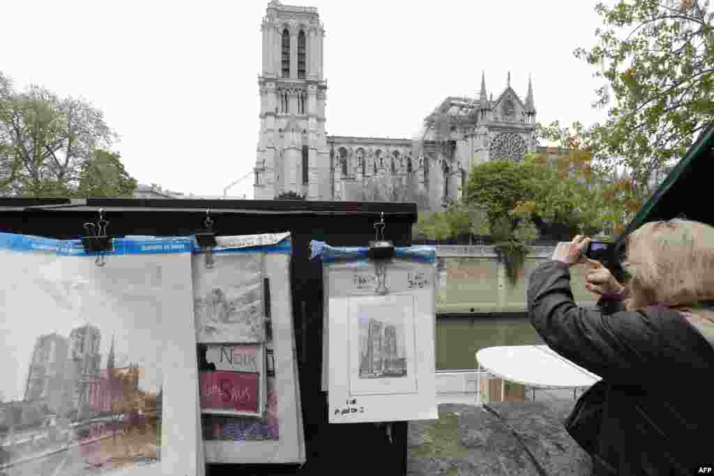 An old picture of Notre-Dame de Paris Cathedral is seen outside the cathedral, one day after a fire devastated the 12th-century landmark in central Paris, France.