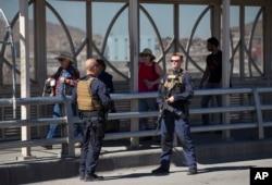 FILE - Pedestrians cross into Juarez, Mexico, as U.S. Customs and Border Protection officers patrol the Paso del Norte Port of Entry in El Paso, Texas, Feb. 16, 2016.