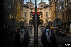 A woman wearing a face mask is reflected in a shop window while walking in Lisbon as Portugal entered a fresh lockdown over a surge in coronavirus cases.