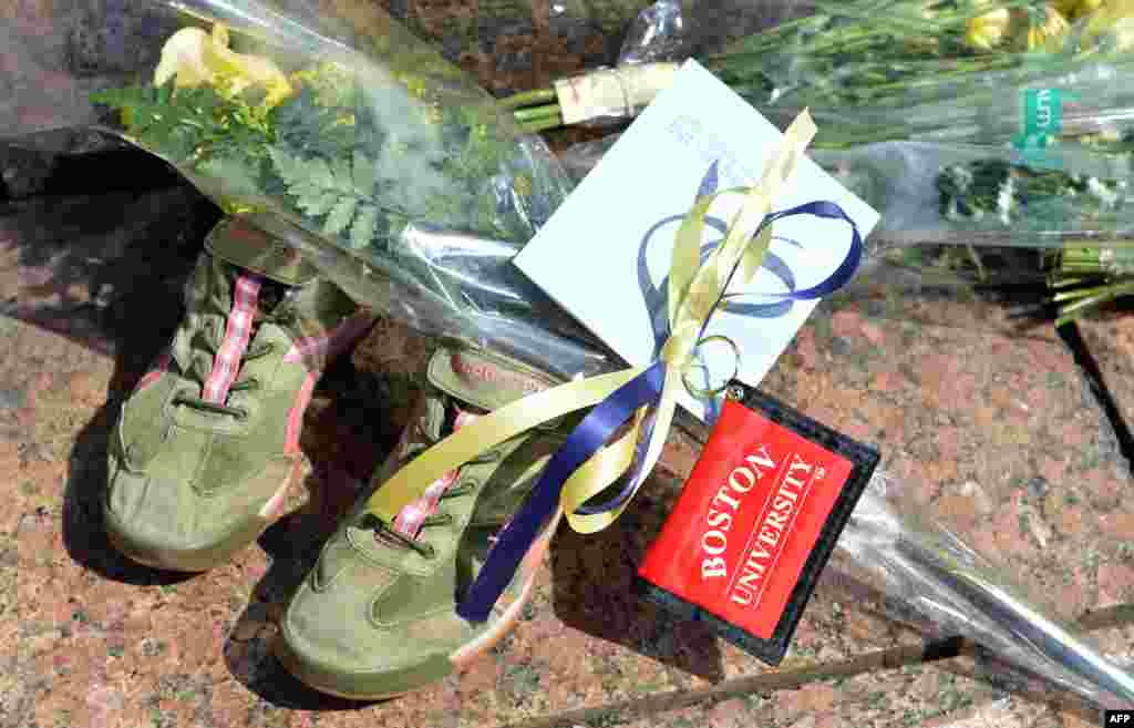 A pair of running shoes, flowers and a Boston University key chain at a makeshift memorial in Boston, Massachusetts, USA, for 23-year-old Lu Lingzi student from China.