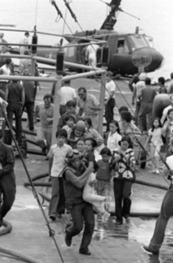 U.S. Marine helicopter crewmen carry Vietnamese civilians to safety aboard the U.S.S. Blue Ridge on April 29, 1975. Their evacuation helicopter crashed on the deck of the amphibious command ship.