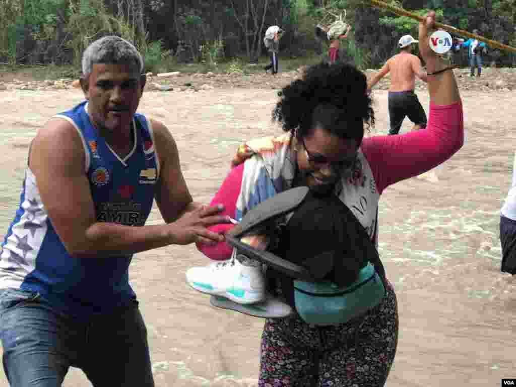 Un hombre ayuda a una mujer que cruza el río Táchira, en la frontera entre Colombia y Venezuela, el martes 2 de abril de 2019.
