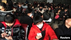 FILE: Passengers wearing masks are seen at the waiting area for a train to Wuhan at the Beijing West Railway Station, ahead of the Chinese Lunar New Year, in Beijing, China January 20, 2020. (REUTERS/Stringer)