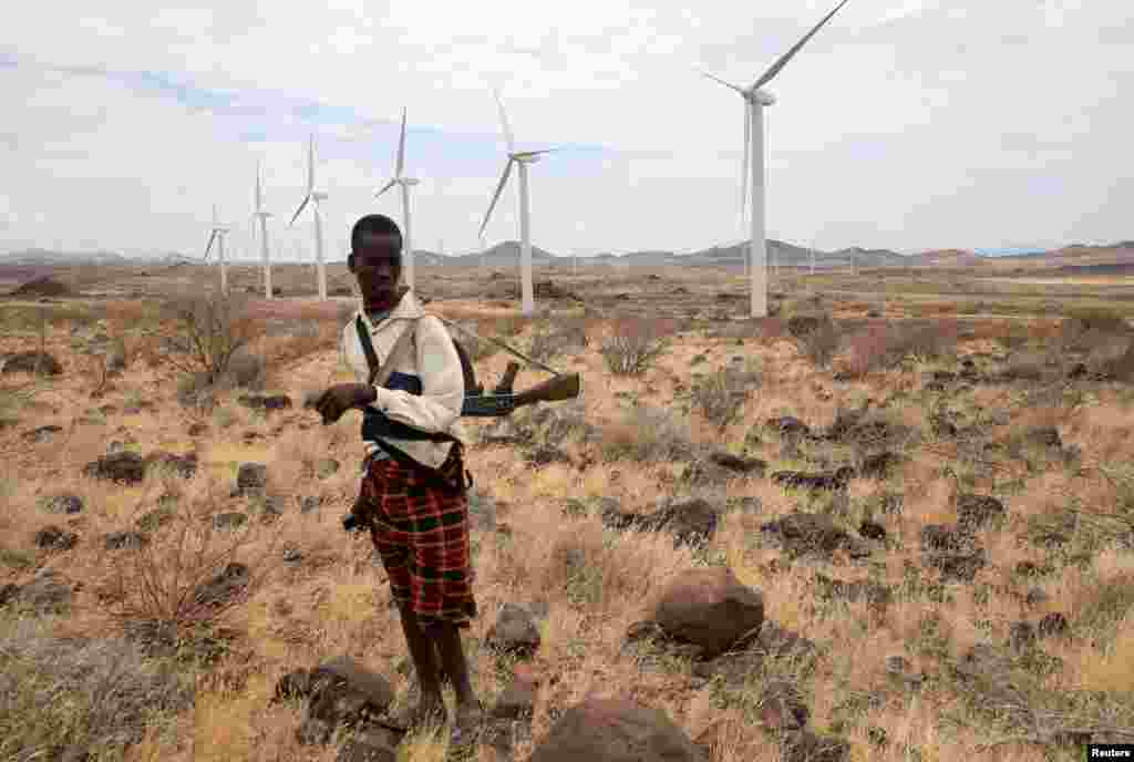 A Turkana herdboy carries his rifle as he herds his goats near the power-generating wind turbines at the Lake Turkana Wind Power project (LTWP) in Loiyangalani district, Marsabit County, Kenya, Sept. 4, 2018.