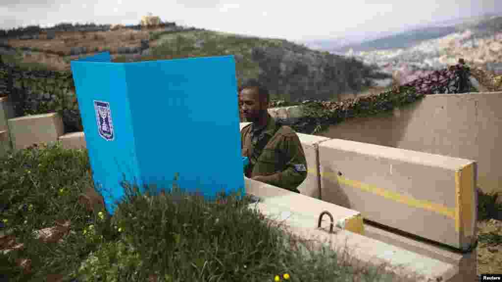 Un soldat israélien place son bulletin de votre dans l'urne pour l'élection parlementaire dans un bureau de vote mobile à la base militaire sur le mont Garizim, près de la ville de Naplouse en Cisjordanie, le 17 mars 2015.