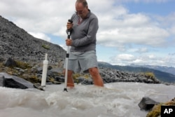 FILE - Scientist Oliver Grah measures the speed of a melt water stream from Sholes Glacier on one of the slopes on Mount Baker in Washington, Aug. 7, 2015. Glaciers on this and other mountains in the North Cascades are thinning and retreating.
