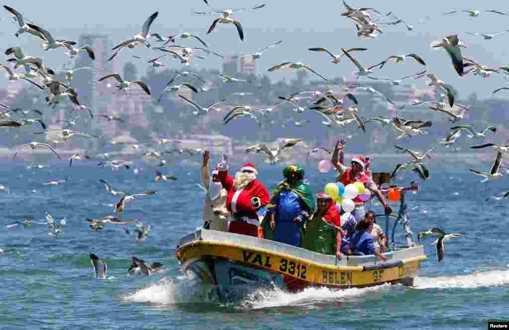 چلی کے ایک ساحلی علاقے میں سانتا کلاز کا بھیس بدلے کشتی پر سوار ایک شخص لوگوں کو دیکھ کر ہاتھ ہلا رہا ہے۔